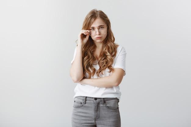 Une étudiante blonde en détresse et épuisée expire stressée, l'air non amusée