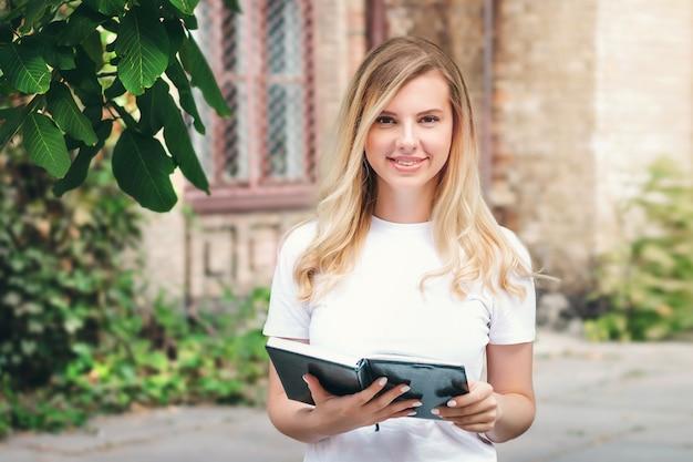 Étudiante blonde se tient avec un livre