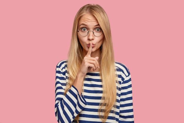 Étudiante blonde secrète posant contre le mur rose