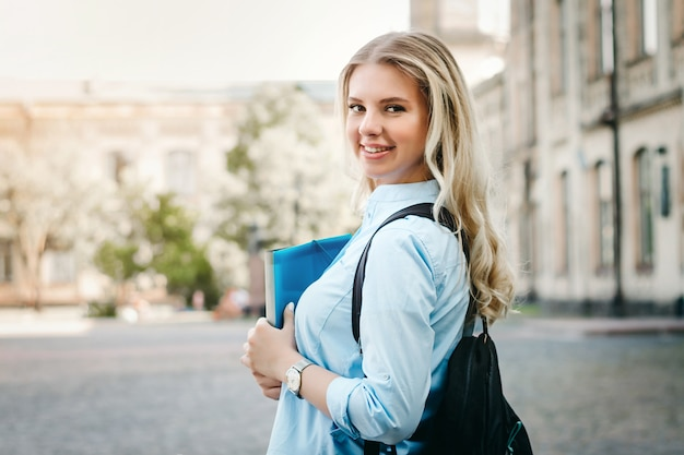Une étudiante blonde sourit et tient un dossier et un cahier à la main sur un fond universitaire