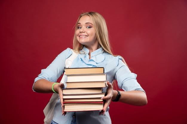 Étudiante blonde tenant une pile de livres et semble positive.