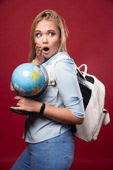 Une étudiante blonde tient un globe et a l'air surprise.