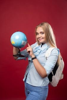 Une étudiante blonde tient un globe et pointe un endroit.