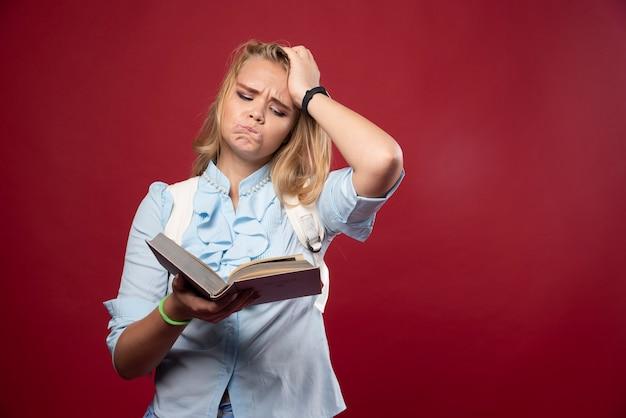 Une étudiante blonde tient ses livres et a l'air terrifiée.