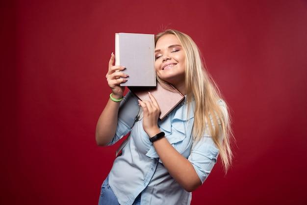 Une étudiante blonde tient ses livres et se sent heureuse.