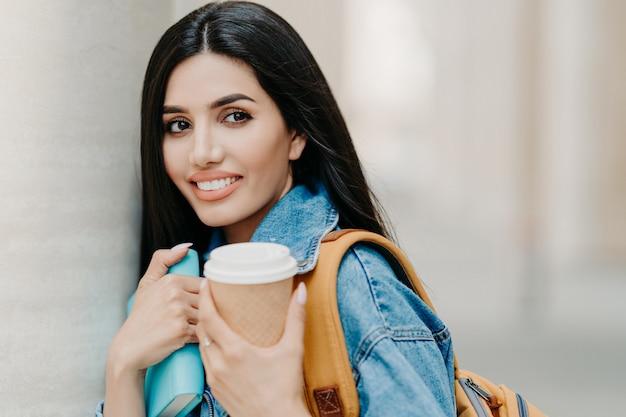 Étudiante brune avec le maquillage, cheveux longs noirs, vêtue d'une veste en jean, contient du café à emporter