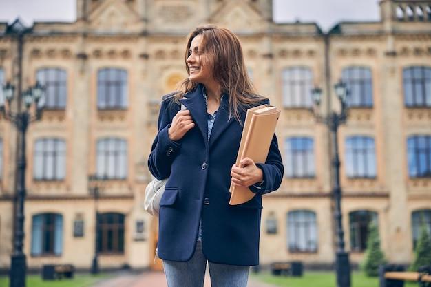 Étudiante brune mignonne avec des dossiers et un sac derrière son dos rentrant chez elle après avoir étudié à l'université