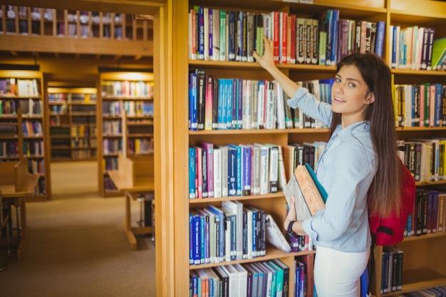 Étudiante brune souriante choisissant un livre dans la bibliothèque