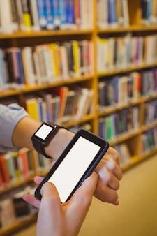 Étudiante brune utilisant sa montre intelligente et son smartphone dans une bibliothèque