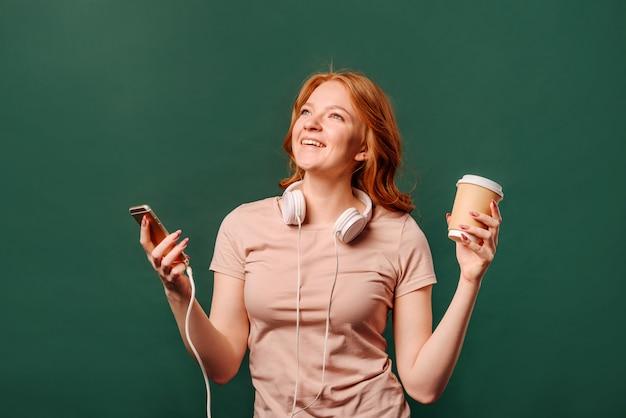 Étudiante avec casque et smartphone souriant, tenant une tasse de papier à la main avec du café ou du thé, debout contre un mur vert avec un espace pour le texte.
