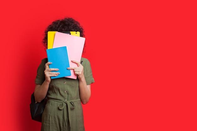 Une étudiante caucasienne aux cheveux bouclés se cache à l'aide de quelques livres tout en posant sur un mur rouge avec de l'espace libre