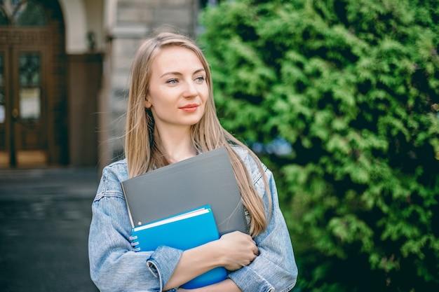 Une étudiante caucasienne se tient devant l'université