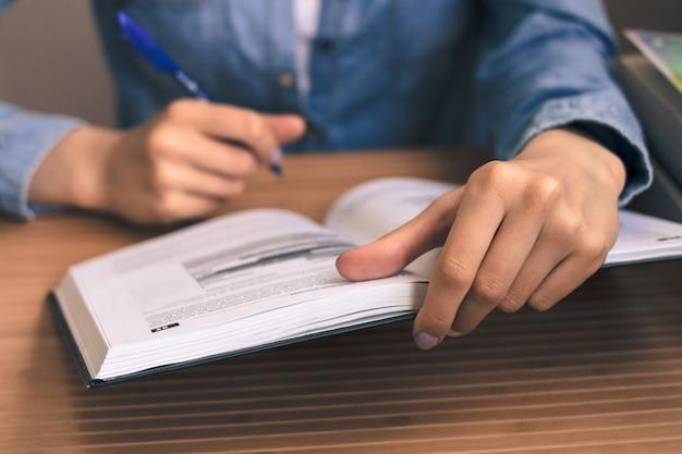 Étudiante dans une chemise en jean bleue, assise à une table en bois et lisant un manuel