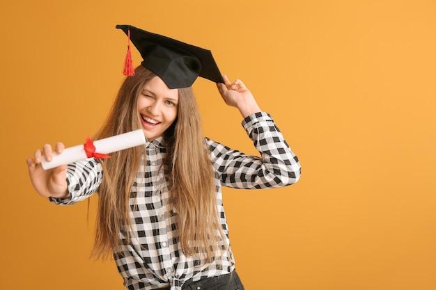 Étudiante diplômée avec diplôme sur fond de couleur
