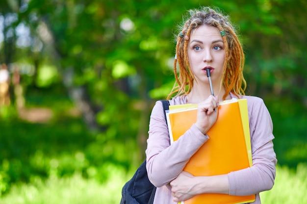 Étudiante avec des dossiers et sac à dos dans le parc d'été vert. éducation, campus et concept d'adolescent