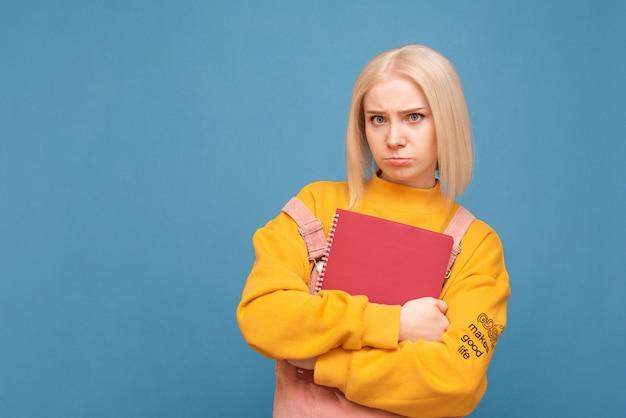 Étudiante drôle se tient sur un fond bleu, tient des livres et des livres dans ses mains et regarde tristement