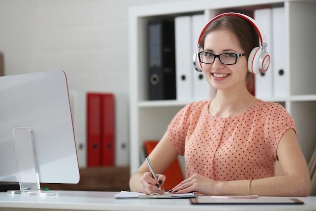 Une étudiante avec des écouteurs écoutant de la musique et apprenant tient la poignée dans sa main et regarde la caméra