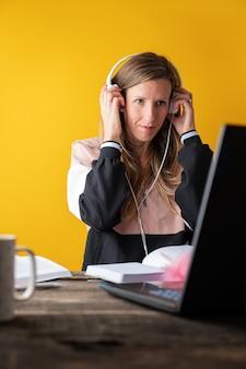 Étudiante avec des écouteurs écoutant un séminaire en ligne sur un ordinateur portable dans l'éducation à la maison image conceptuelle.