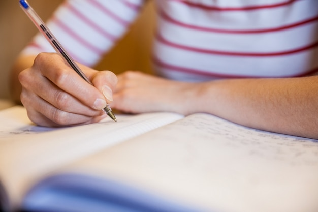 Étudiante écrivant des notes à l'université