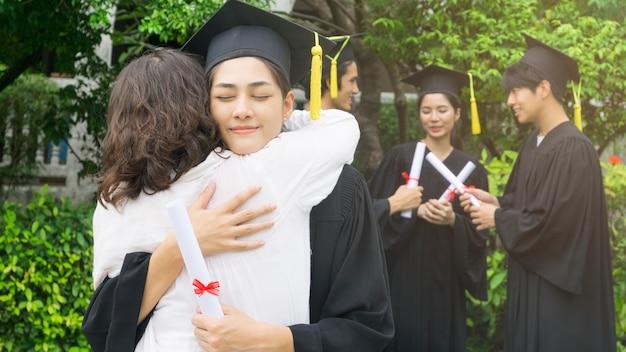 Étudiante embrasse le parent dans la cérémonie de félicitations.