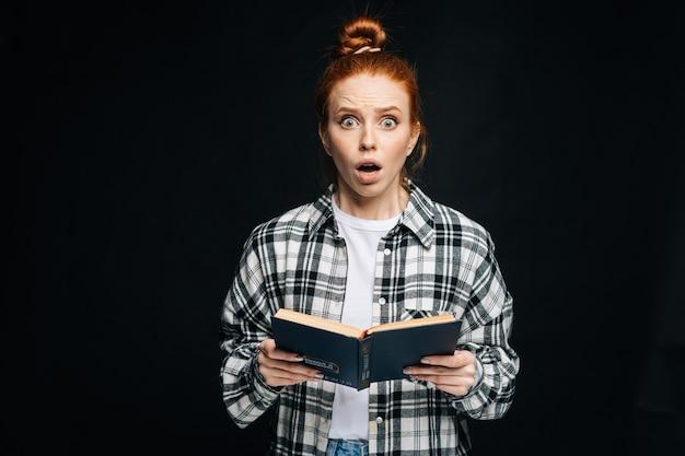 Étudiante étonnée de jeune femme avec la bouche ouverte tenant des livres et regardant la caméra