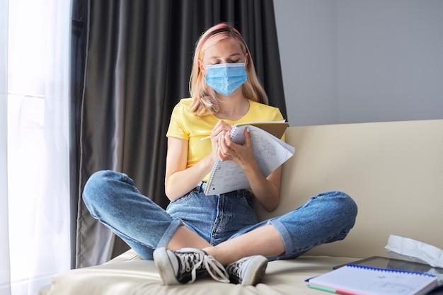 Étudiante en études de masque médical de protection, écrit dans un cahier tout en étant assise sur un canapé à l'intérieur