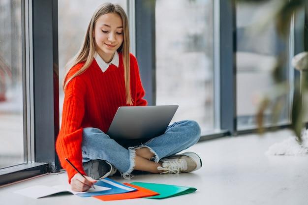 Étudiante étudiant sur l'ordinateur par la fenêtre