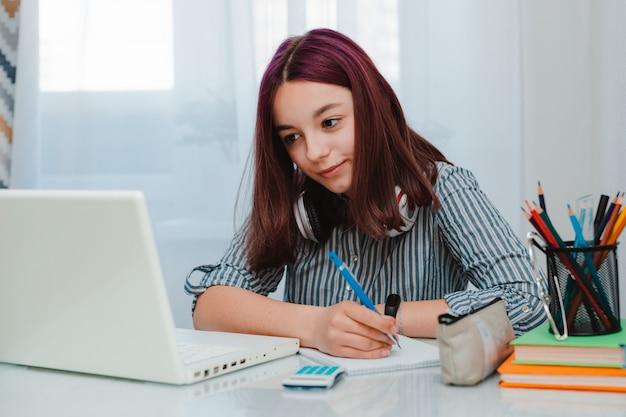 Étudiante étudiante travaillant à domicile avec ordinateur portable à faire leurs devoirs