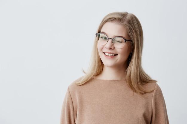 Étudiante européenne coquette et positive avec des cheveux blonds et raides souriant joyeusement, clignotant de manière ludique, flirtant avec vous. expressions faciales et émotions humaines