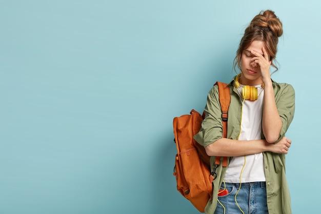 Une étudiante fatiguée a une expression endormie, essaie de se rafraîchir avec de la musique dans des écouteurs, porte un sac à dos, porte des vêtements décontractés