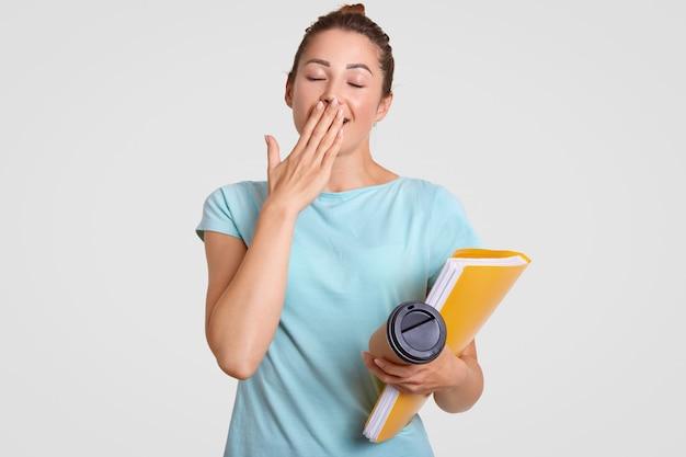 Une étudiante fatiguée et surmenée a une expression endormie, bâille lorsque les besoins se reposent, couvre la bouche avec la paume, tient un café à emporter et un dossier, isolé sur blanc. concept de personnes et de délais