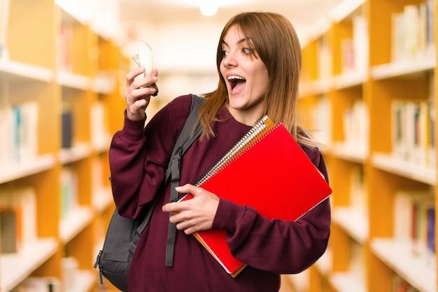 Étudiante femme tenant une ampoule sur fond flou. retour à l'école