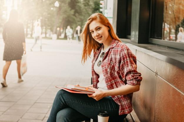 Étudiante fille souriante rousse attrayant habillé de vêtements décontractés à la rue en ville