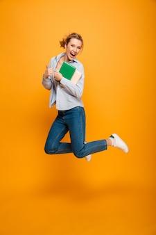Étudiante heureuse jeune femme sautant montrant les pouces vers le haut.