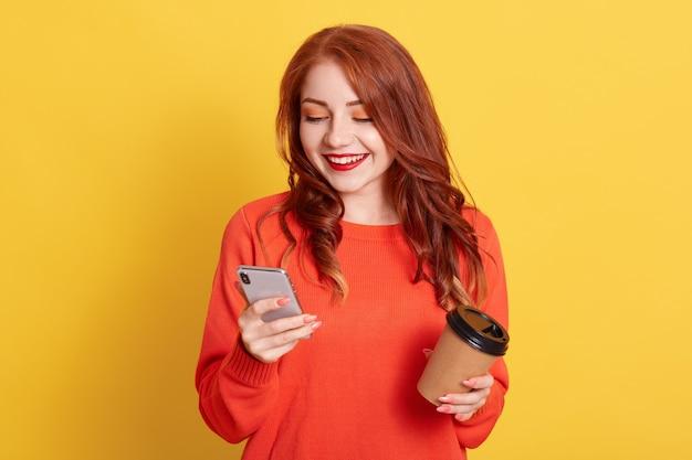 Une étudiante heureuse prend une pause-café après les cours, profite de son temps libre, utilise un téléphone portable pour discuter en ligne, regarde un appareil, tient un gobelet jetable avec une boisson chaude, se tient contre un mur jaune.
