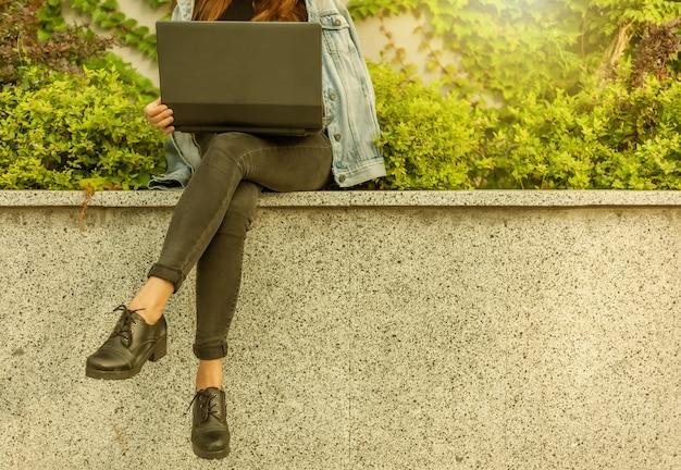 Une étudiante heureuse en veste en jean et lunettes utilise un ordinateur portable tout en étant assise dans le parc de la ville. recadrer la photo