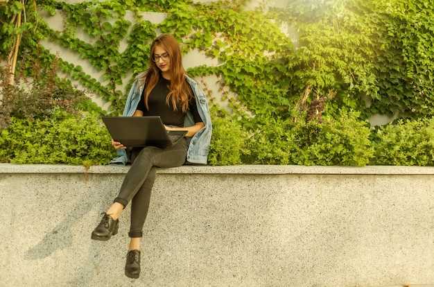 Une étudiante heureuse en veste en jean et lunettes utilise un ordinateur portable tout en étant assise dans le parc de la ville