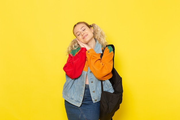Étudiante jeune dans des vêtements modernes se présentant comme doux dormir sur jaune