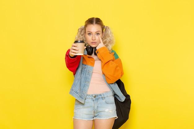 Étudiante jeune dans des vêtements modernes tenant du café et posant sur jaune