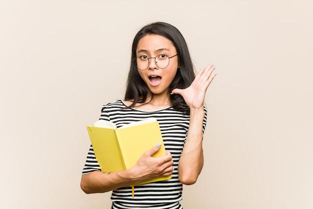 Étudiante jeune femme asiatique tenant un livre surpris et choqué.