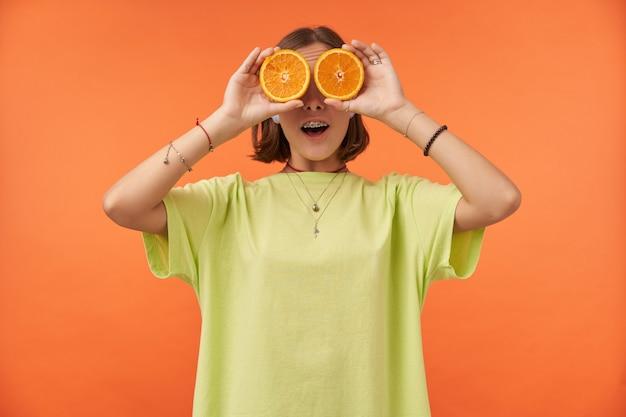 Étudiante, jeune femme aux cheveux bruns courts tenant des oranges sur ses yeux. regard surpris. debout sur un mur orange. porter un t-shirt vert, des orthèses dentaires et des bracelets