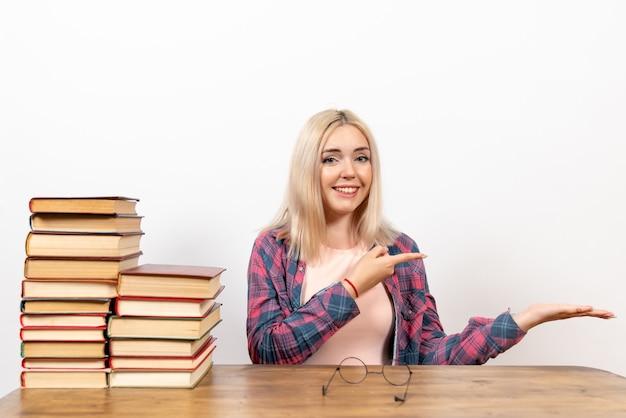 Étudiante juste assise avec des livres sur blanc