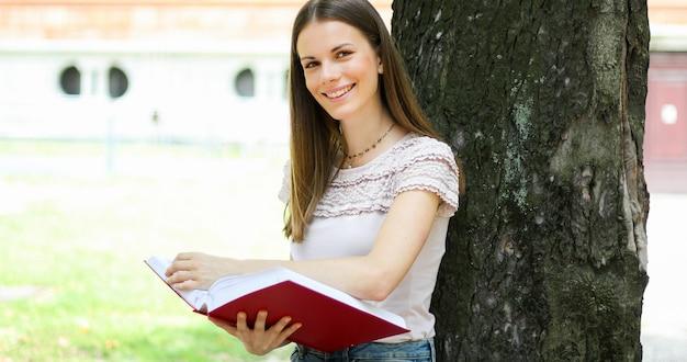 Étudiante en lisant un livre en plein air dans le parc se trouvant contre un arbre et souriant
