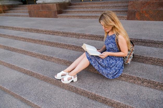 Étudiante lisant sur les marches de l'université.