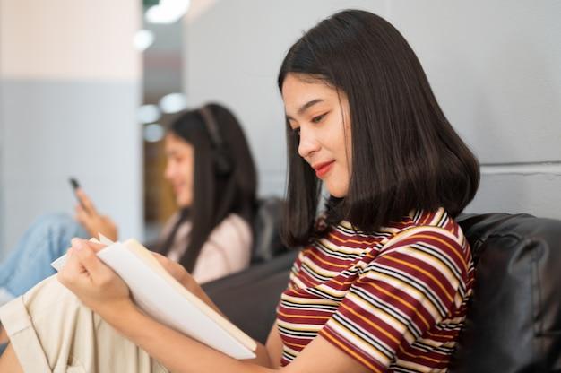 Une étudiante lit un livre à la bibliothèque