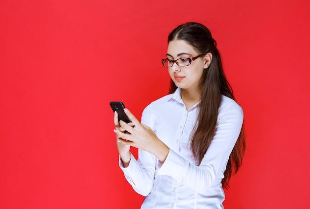 Étudiante à lunettes discutant avec son smartphone.