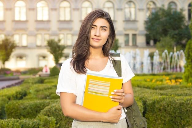 Une étudiante à lunettes avec des livres dans les mains près du campus.