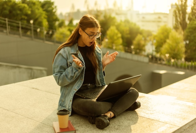 Une étudiante moderne surprise dans une veste en jean assise dans les escaliers regarde un ordinateur portable à écran en plein air. apprentissage à distance. concept de jeunesse moderne.