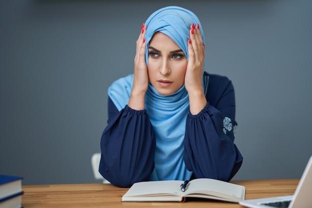 Étudiante musulmane malheureuse apprenant dans la bibliothèque