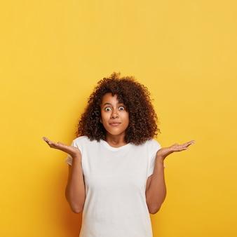 Une étudiante perplexe, incertaine, écarte les paumes sur le côté, regarde avec des yeux écarquillés, n'a aucune idée et n'est pas au courant, a les cheveux foncés et bouclés, porte un t-shirt blanc, pose contre un mur jaune, espace libre vers le haut